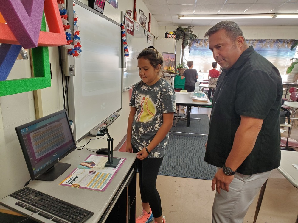 CIS Coach Brown shows Kenzi Fourkiller how his new document camera works.
